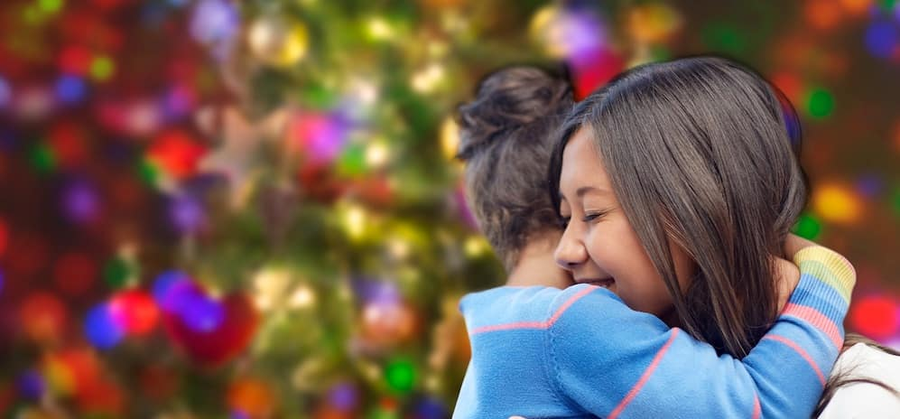 Mom and daughter hugging in front of Christmas lights