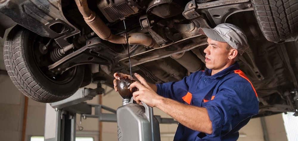 Mechanic Draining Oil from Vehicle