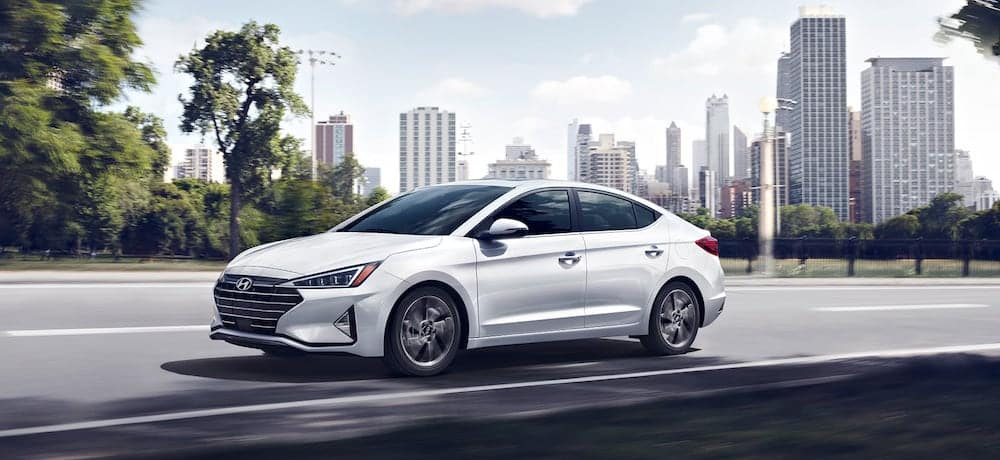 A 2020 Hyundai Elantra driving with a city skyline in the background