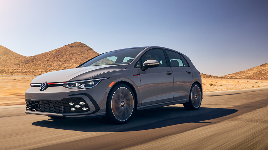 2022 Volkswagen Golf GTI in the color Moonstone Gray on a highway with hills in the background.
