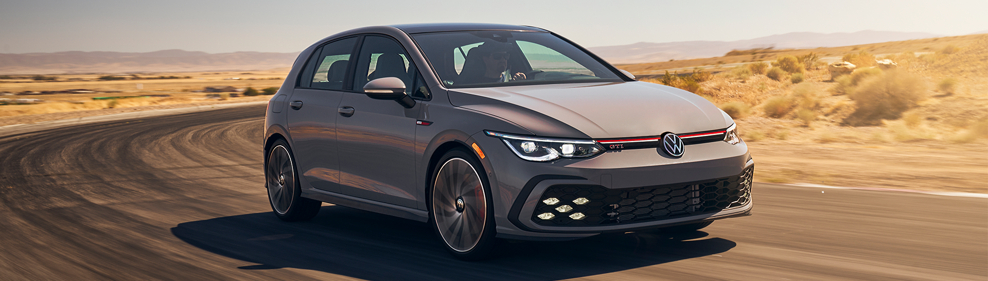 2022 Volkswagen Golf GTI in the color Moonstone Gray driving on a road.