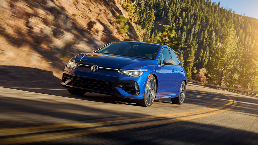 2022 Volkswagen Golf R in the color Lapiz Blue Metallic driving along mountain road.