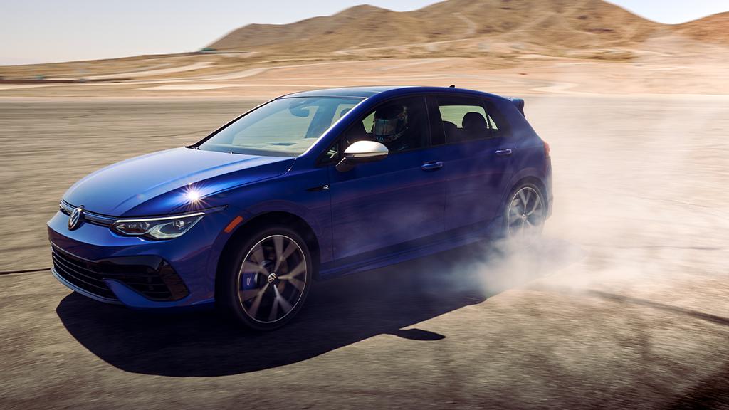2022 Volkswagen Golf R in the color Lapiz Blue Metallic burning rear tires.