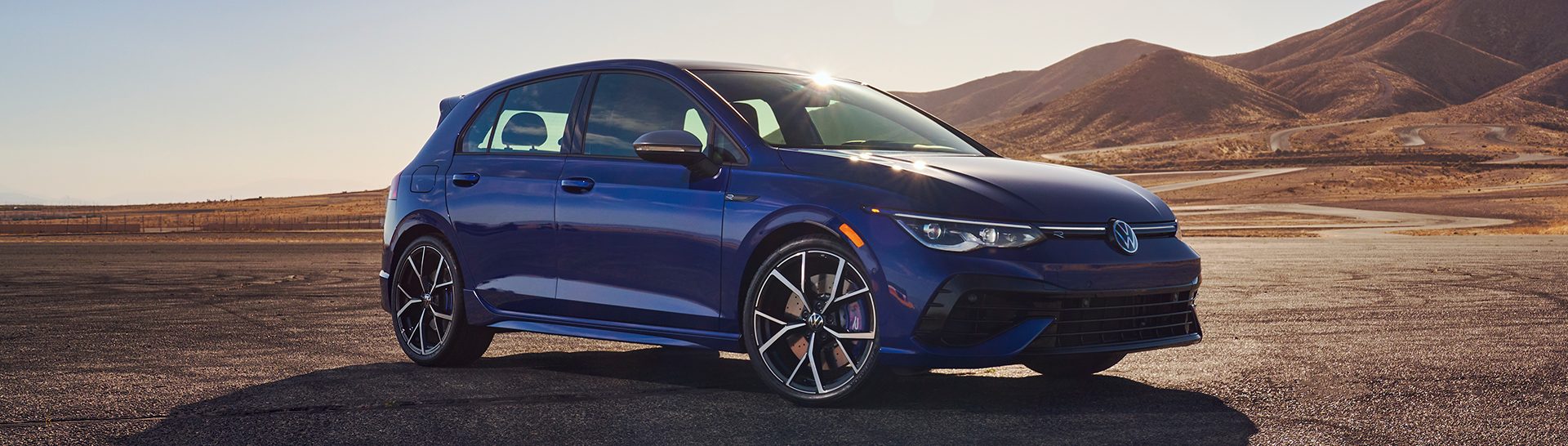 2022 Volkswagen R in the color Lapiz Blue Metallic parked on a lot with hills in the background.
