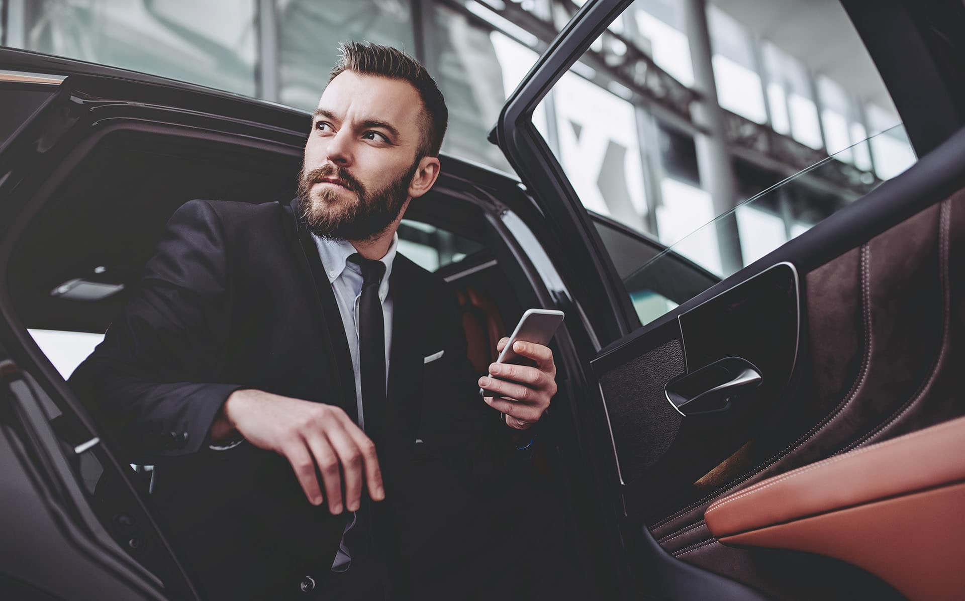Young handsome businessman is sitting in luxury car. Serious bearded man in suit with smart phone in hands.