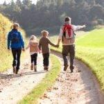 Two parents walking with two kids at the park