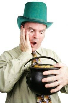 Man Dressed As Leprechaun Looking At A Pot Of Gold