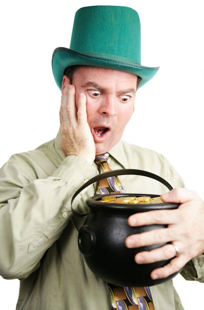 Man Dressed As Leprechaun Looking At A Pot Of Gold - Facts About St. Patrick's Day