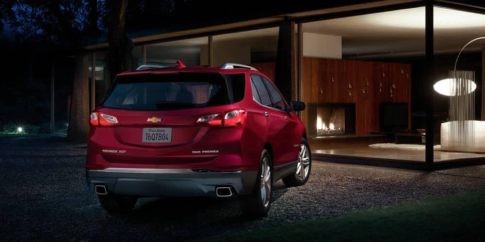 Red 2020 Chevy Equinox parked outside modern home at night