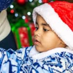 Young boy in Santa hat helping with Christmas