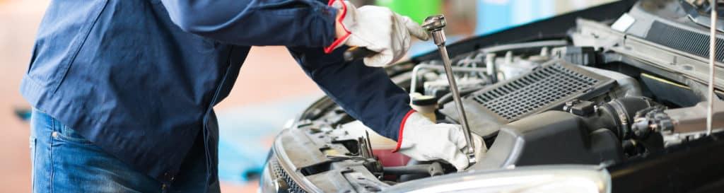 mechanic working under hood of car