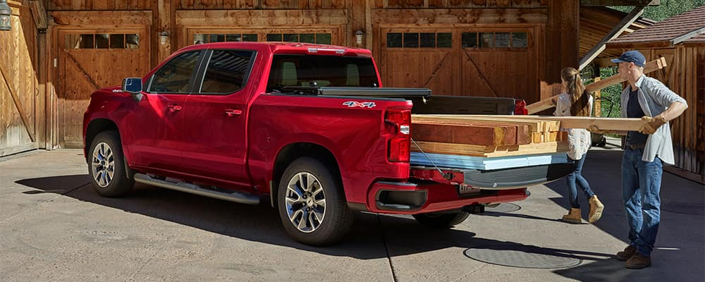 Couple Taking Wood Boards Out of Chevrolet Silverado