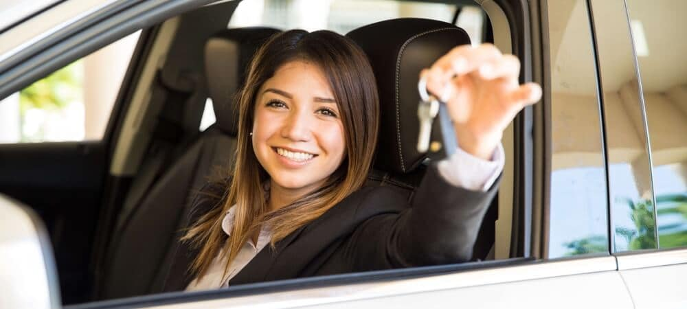woman smiling as she holds her car keys