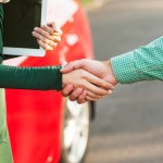 Business handshake to close the deal after buying a car, between a man and a woman