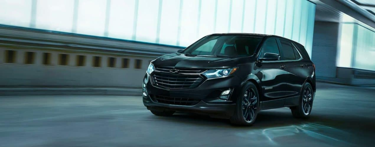 A black 2021 Chevy Equinox Midnight Edition is shown driving through a tunnel.
