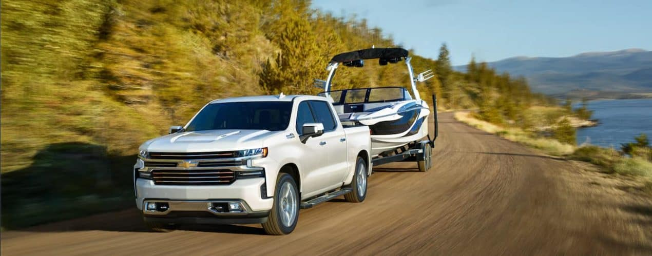 A white 2021 Chevy Silverado 1500 is shown towing a boat past a lake.