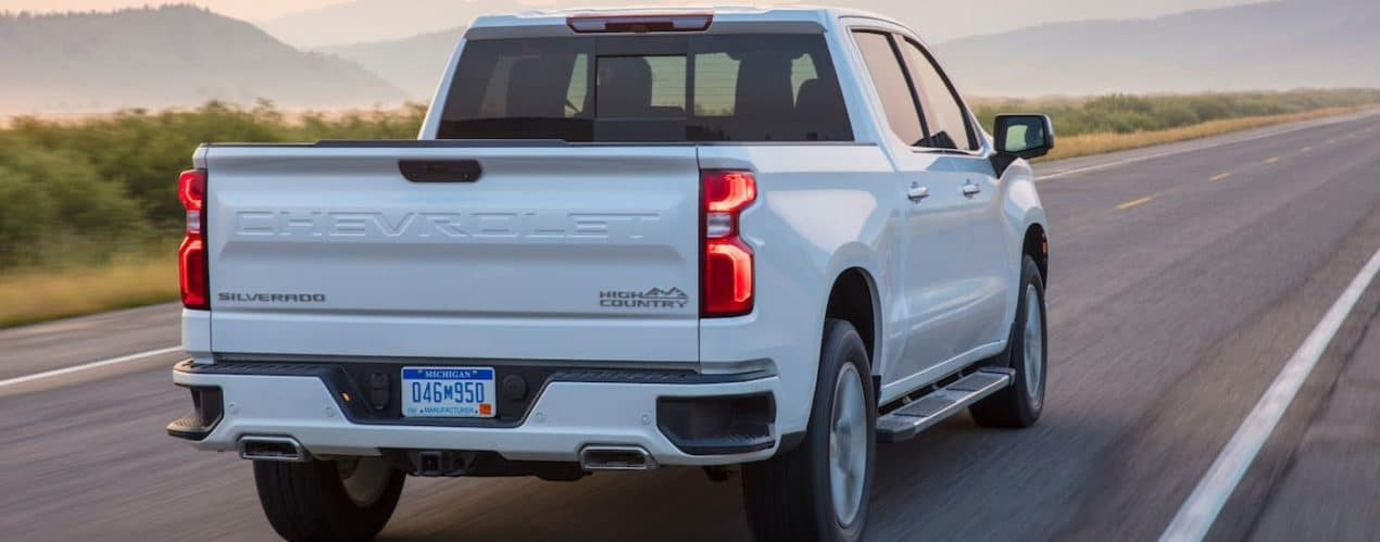 A white 2021 Chevy Silverado 1500 is shown from the rear driving down an empty road.