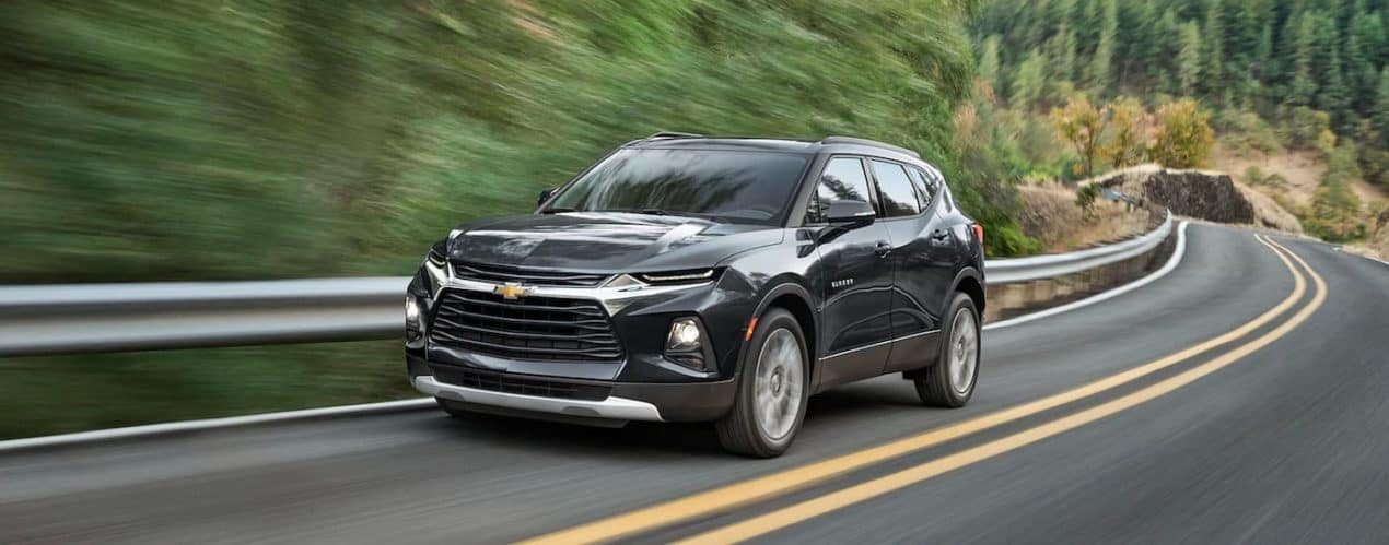 A black 2021 Chevy Blazer is shown speeding down a tree-lined road.