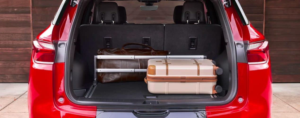 Luggage is shown in the trunk of a red 2021 Chevy Blazer.