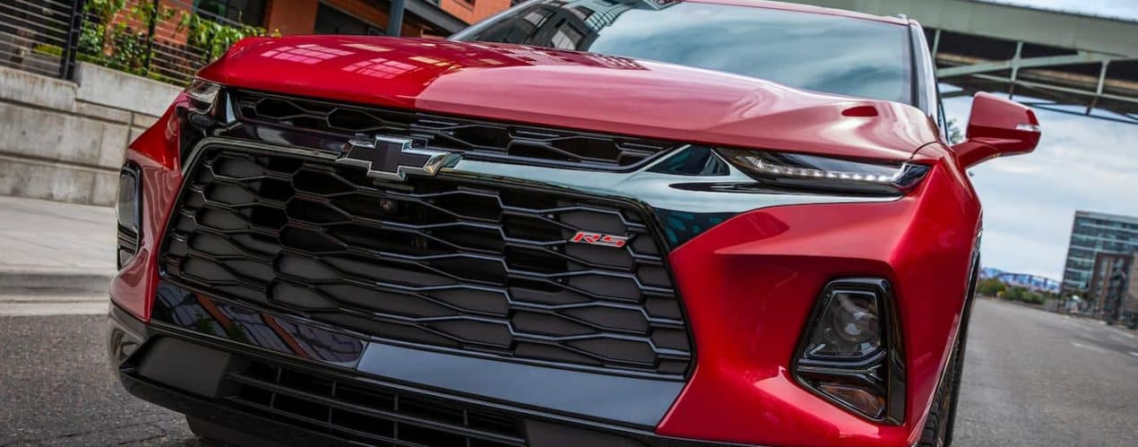 A close up shows the front grille and badging on a red 2021 Chevy Blazer RS.