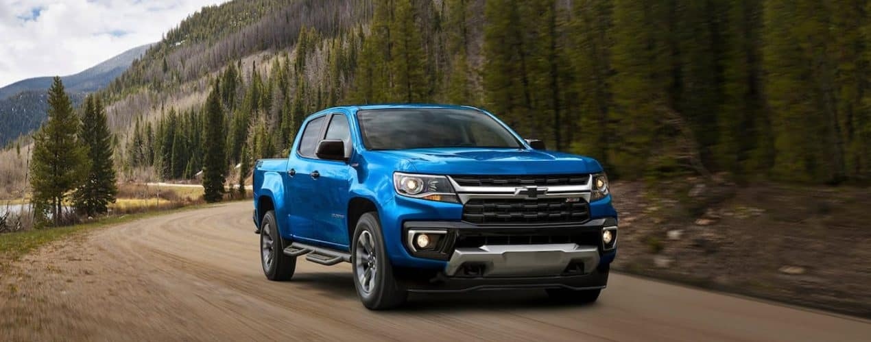 A blue 2021 Chevy Colorado Z71 is shown driving down a dirt path next to a lake and trees.