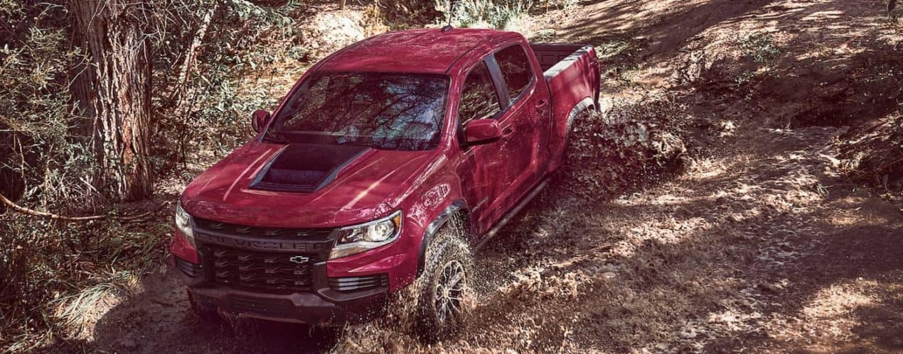 A black and red 2021 Chevy Colorado ZR2 is shown driving through mud in the woods.