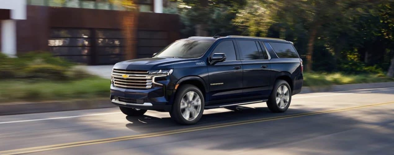 A blue 2021 Chevy Suburban is driving on a neighborhood street.