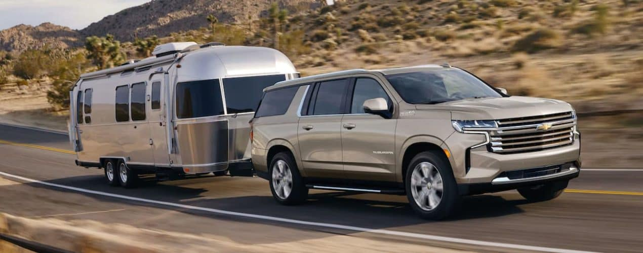 A tan 2021 Chevy Suburban is towing an Airstream on a rural road.