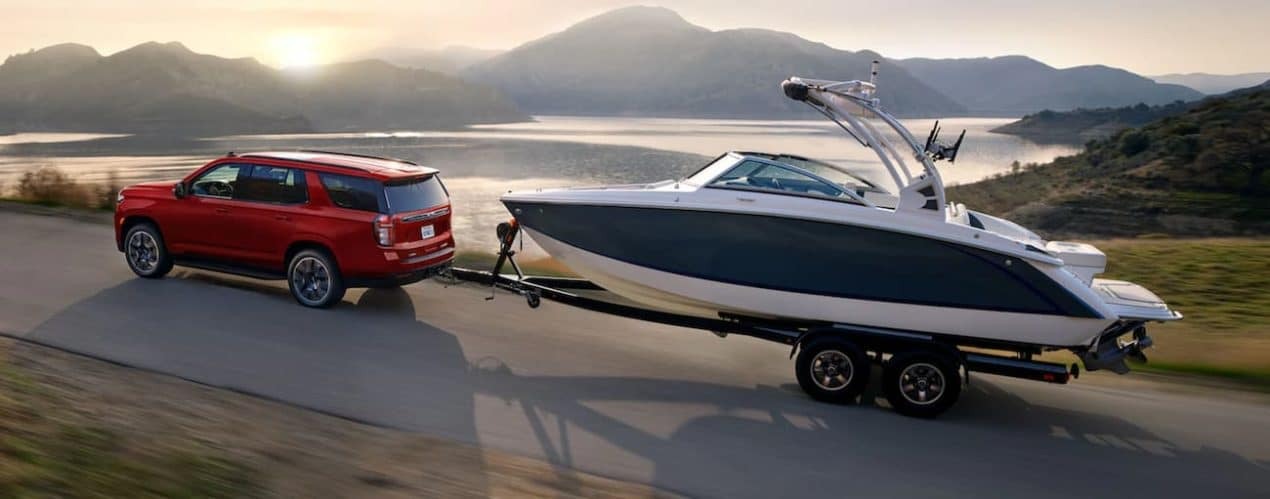 A red 2021 Chevy Tahoe is towing a boat past a lake and mountains.