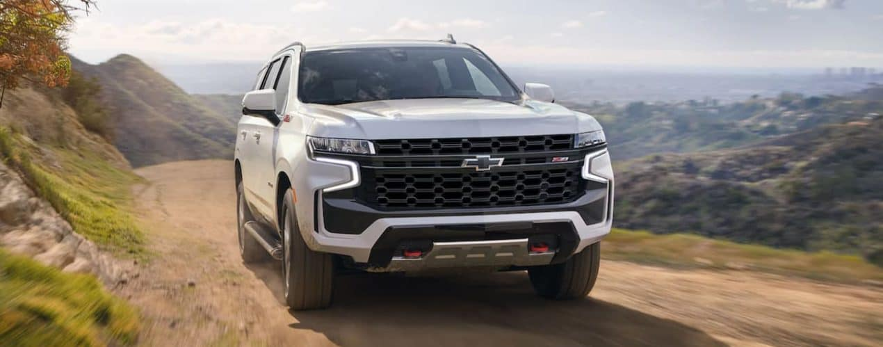A white 2021 Chevy Tahoe is driving on a dirt road past mountains.