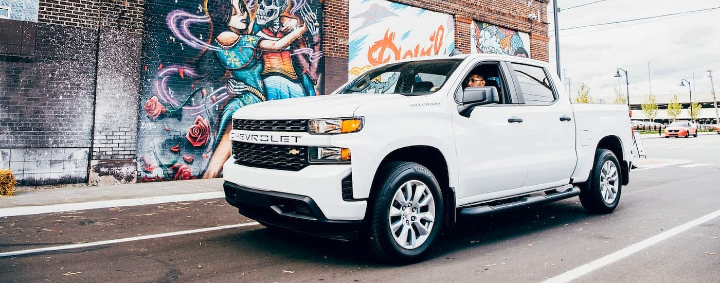 A white 2021 Chevy Silverado 1500 is driving past a mural after leaving an Alabama Chevy dealership.