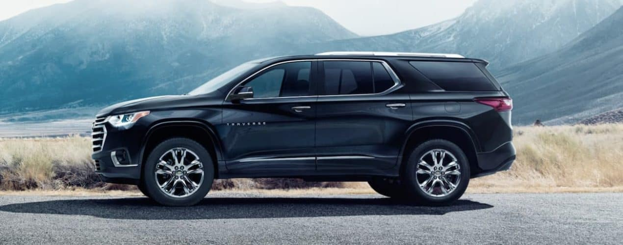 A black 2021 Chevy Traverse is shown from the side parked on the edge of a road overlooking mountains.