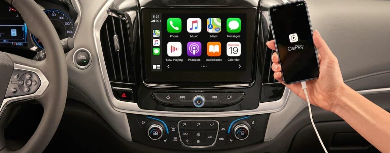 The infotainment screen in a 2021 Chevy Traverse is shown, a hand is holding out a smart phone.