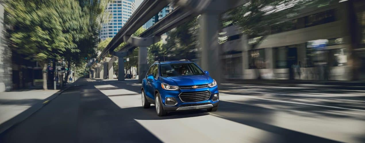 A blue 2021 Chevy Trax is shown driving through a city.