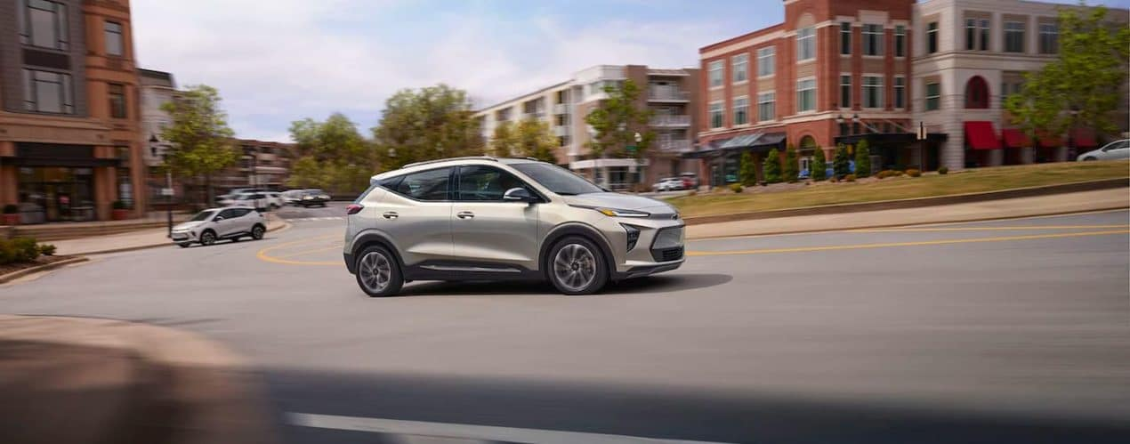 A silver 2022 Chevy Bolt EUV is shown from the side driving through a city.