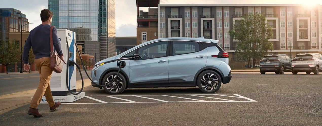 A pale blue 2022 Chevy Bolt EV is shown being approached by a person at a charging station.