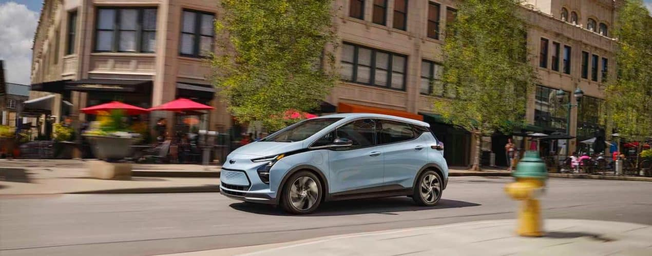 A pale blue 2022 Chevy Bolt EV is shown from the side driving down a city street.