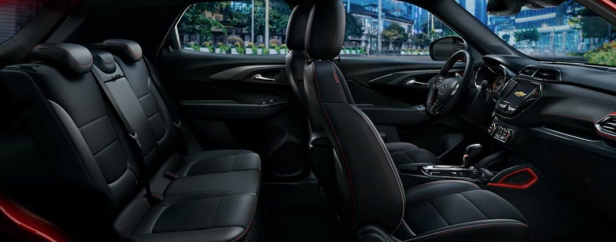 The black interior of a 2022 Chevy Trailblazer shows two rows of seating and the infotainment system.