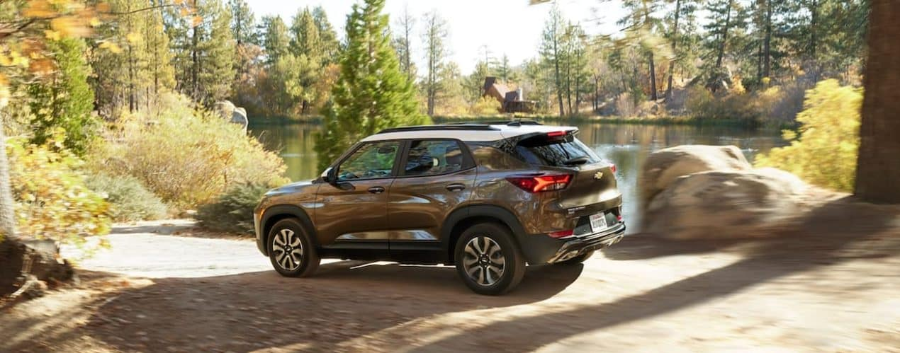 A bronze 2022 Chevy Trailblazer is shown from the side driving past a lake.