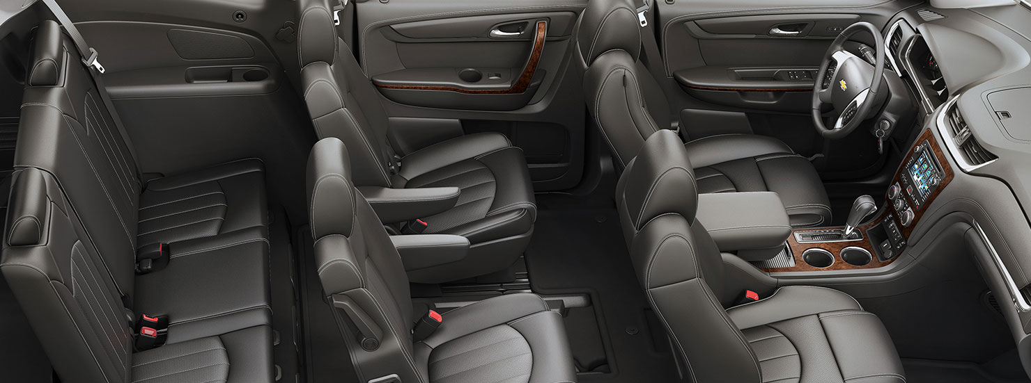 The dark grey interior of a 2016 Chevy Traverse is shown from the side.