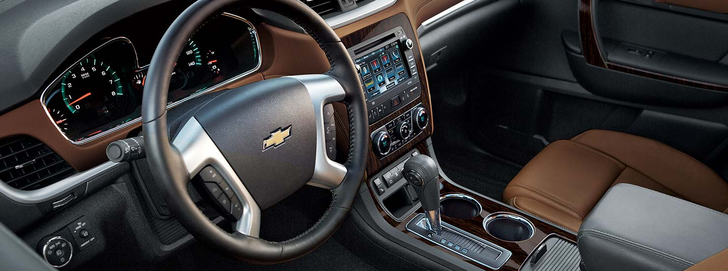 The black and brown steering wheel and dashboard are shown on a 2016 Chevy Traverse.