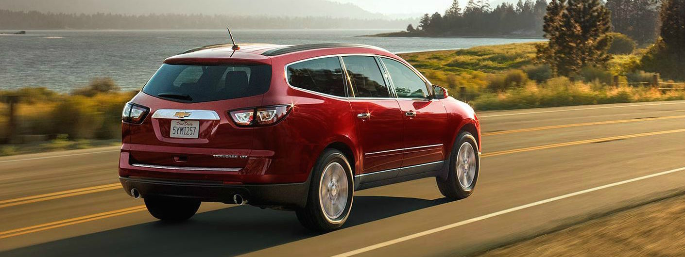 A red 2016 Chevy Traverse is driving past a lake on a sunny day near Albany, NY.