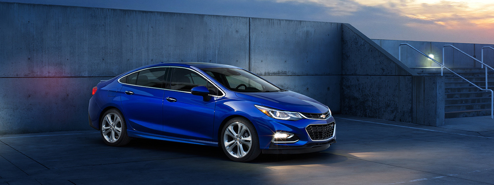 A blue 2016 Chevy Cruze is parked in front or a concrete wall at dusk.