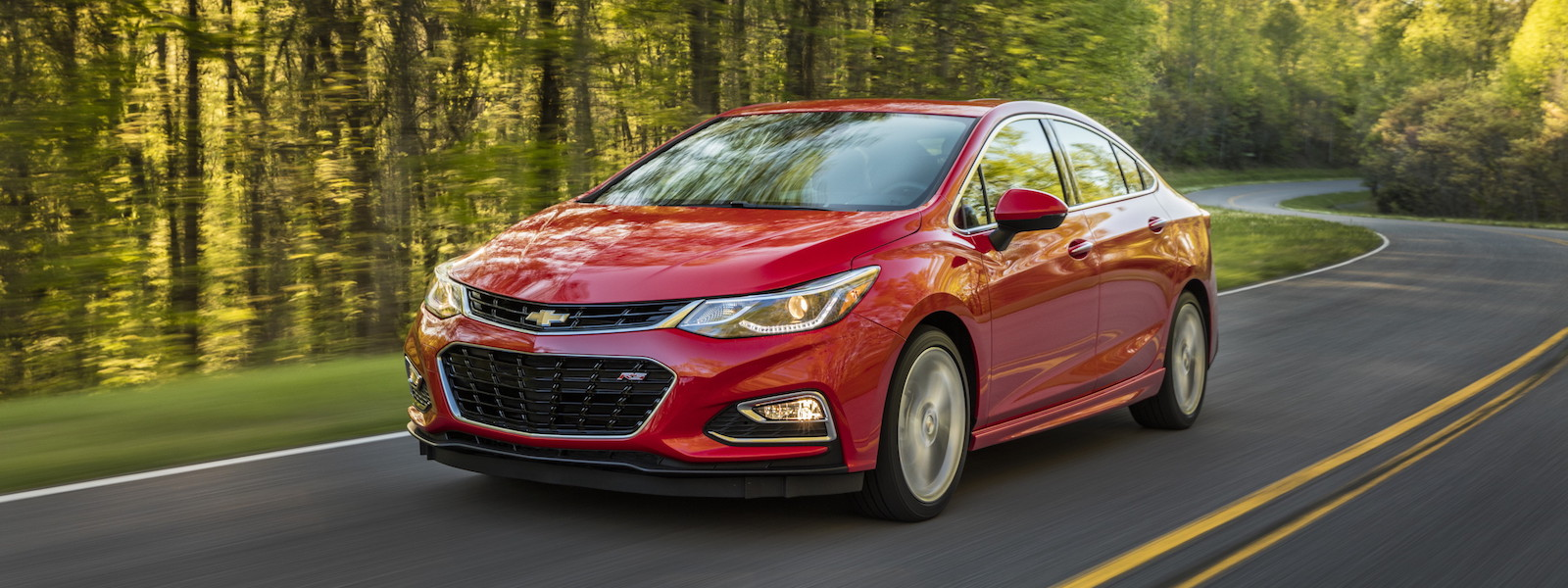 A red 2016 Chevy Cruze is driving on a winding road near Albany, NY.