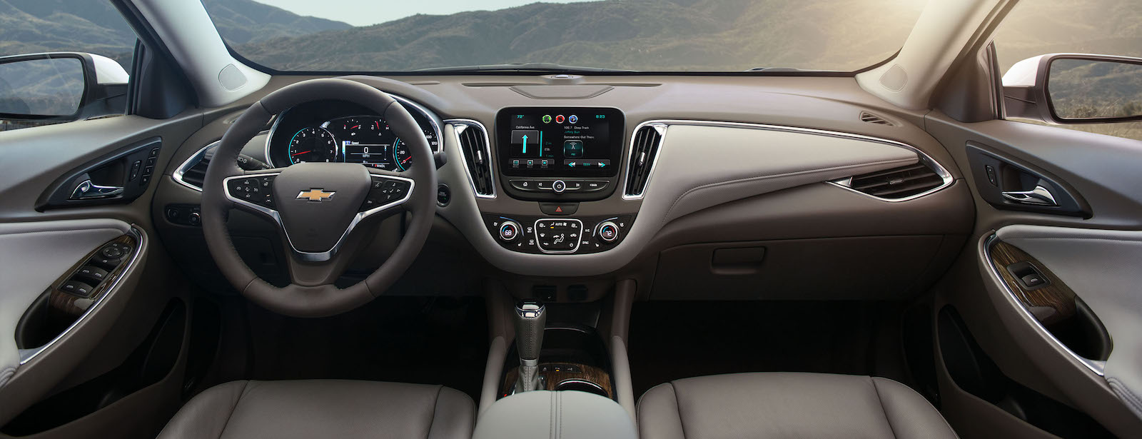 The brown and tan interior of a 2016 Chevy Malibu is shown with mountains near Albany, NY, in the window.