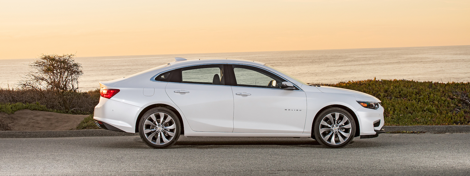 A white 2016 Chevy Malibu is shown from the side in front of the ocean with a yellow sky.