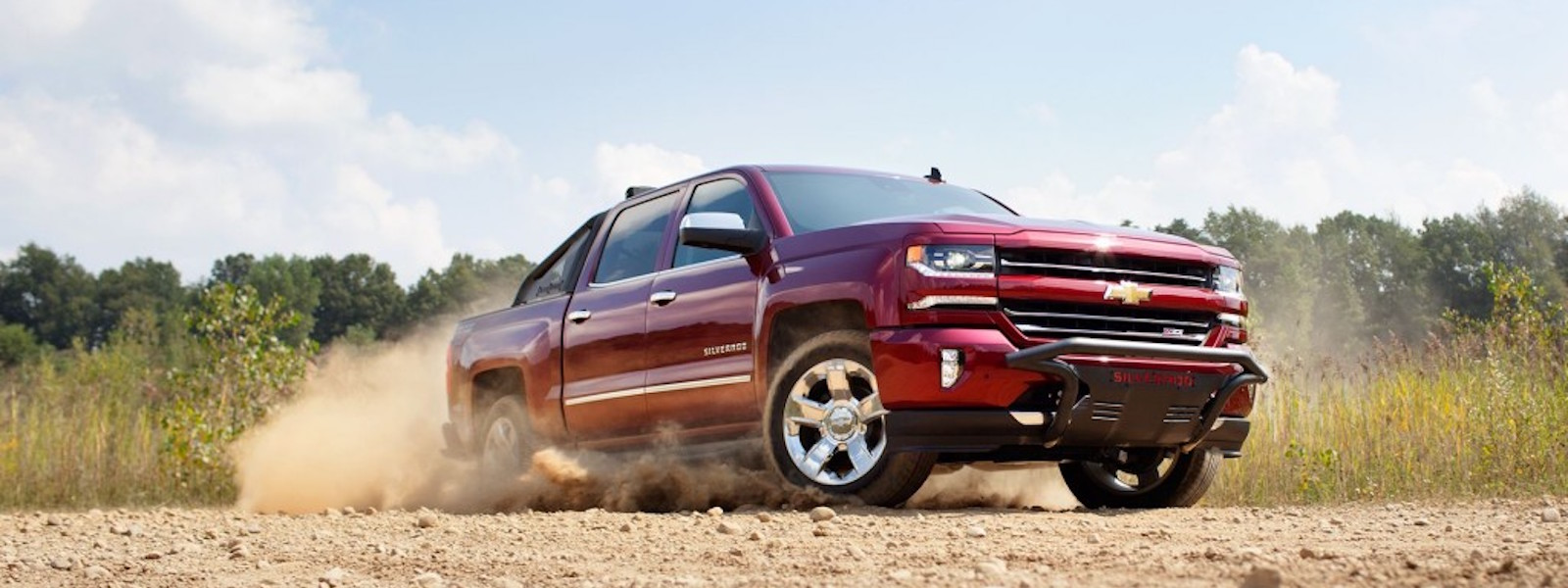 A red 2016 Chevy Silverado is kicking up sand on a dirt road near Albany, NY.
