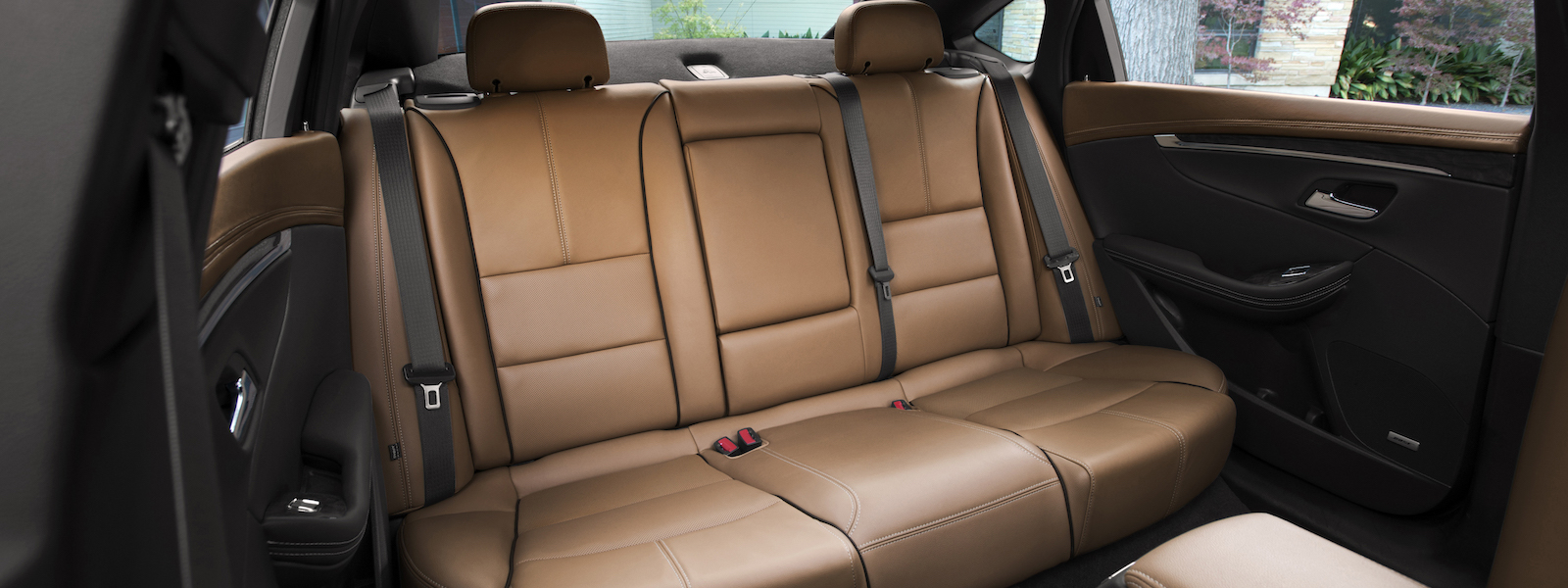 The rear seat of a 2016 Chevy Impala is shown in tan leather.