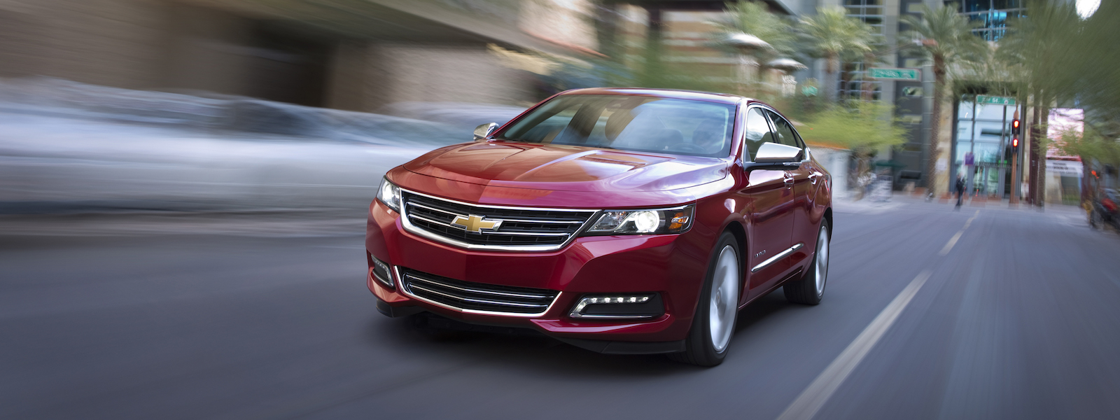 A red 2016 Chevy Impala is driving on a city street in Albany, NY.