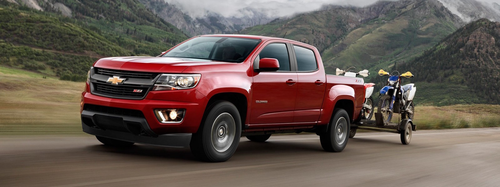 A red 2016 Chevy Colorado is towing dirt bikes on a mountain road.